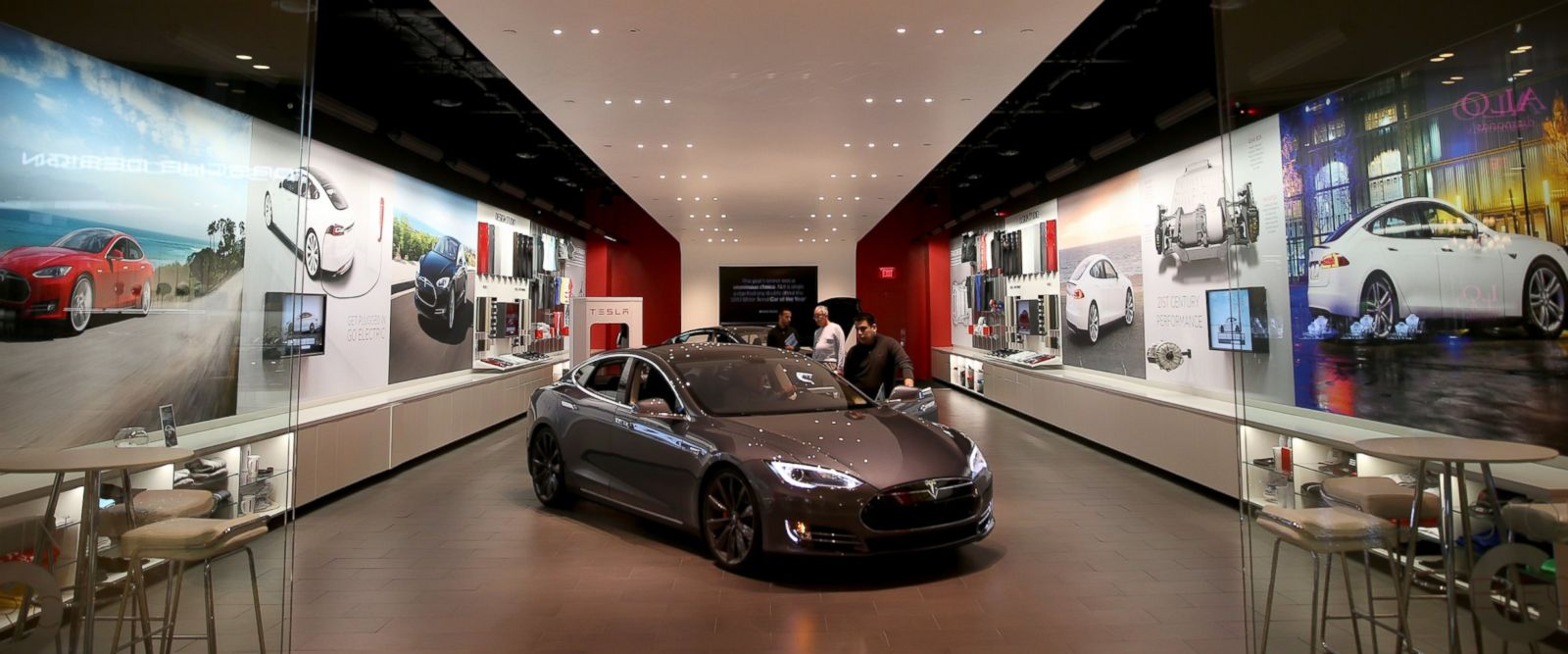 PHOTO: People look at a Tesla Motors vehicle on the showroom floor at the Dadeland Mall in Miami, Fla., Feb. 19, 2014.