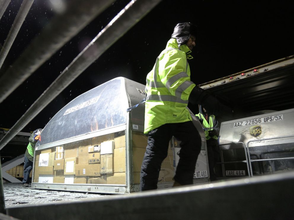 PHOTO: Employees at UPS Logan Airport facility load packages from an early morning plane