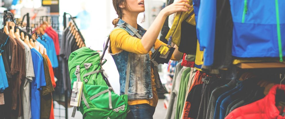 PHOTO: A millennial shops in a travel and outdoor equipment store.