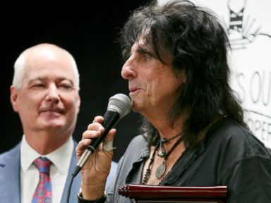 PHOTO: Alice Cooper is inducted into the White Castle Cravers Hall of Fame at the chains home office in Columbus, Ohio, next to Bill Ingram, White Castle CEO.