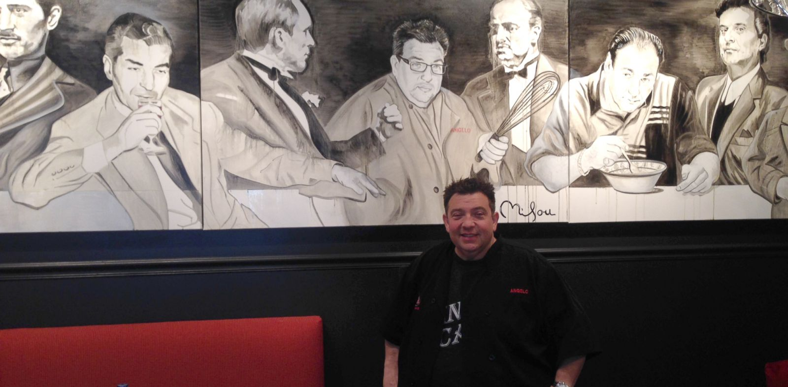 PHOTO: Angelo Lutz, is pictured in front of a mural at his restaurant The Kitchen Consigliere, with depictions of the world-famous real and fictitious gangsters.