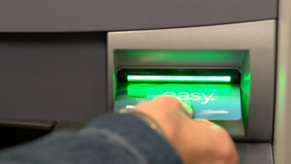 PHOTO: A bank customer swipes his card sideways.