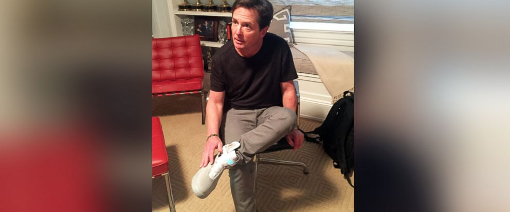 """PHOTO: The MIchael J Fox Foundation shared this image to their Twitter, Oct. 21, 2015, of MIchael J. Fox trying on similar Nike sneakers from the movie """"back to the Future Part II"""" set to be released in 2016."""
