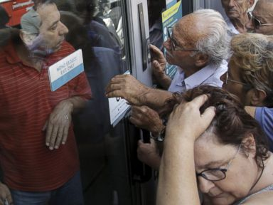 PHOTO: Pensioners waiting outside a closed National Bank branch and hoping to get their pensions argue with a bank employee, left, June 29, 2015, in Iraklio on the island of Crete, Greece.