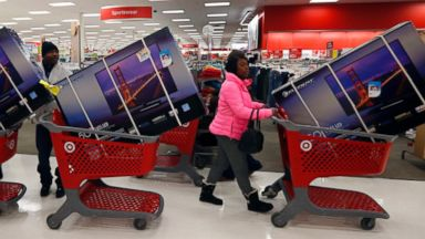 PHOTO: Thanksgiving Day holiday shoppers line up with television sets on discount at the Target retail store in Chicago, Nov. 28, 2013.