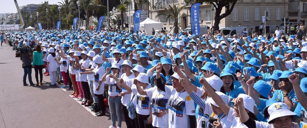 PHOTO: Employees of Chinese company Tiens attend a parade on the Promenade des Anglais in Nice, southeastern France, May 8, 2015.