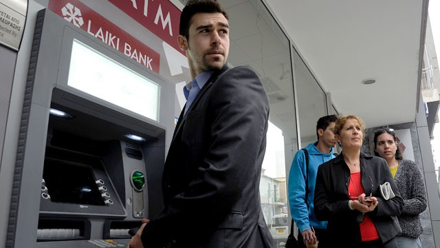 PHOTO: People wait to use the ATM of a closed branch of Laiki Bank in southern port city of Limassol, Cyprus on March 21, 2013.