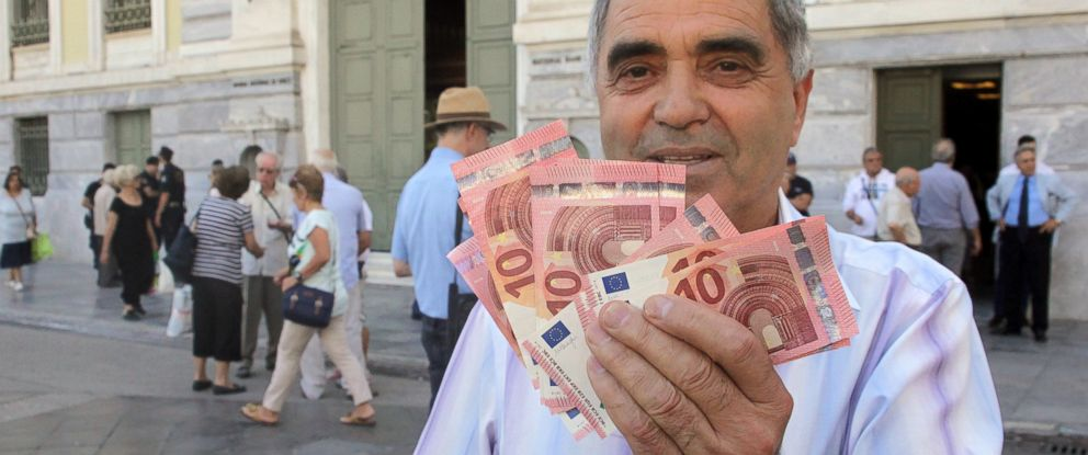 PHOTO: Pensioner Giorgos Petropoulos shows ten euros notes who receive from National Bank of Greece in Athens, July 1, 2015.
