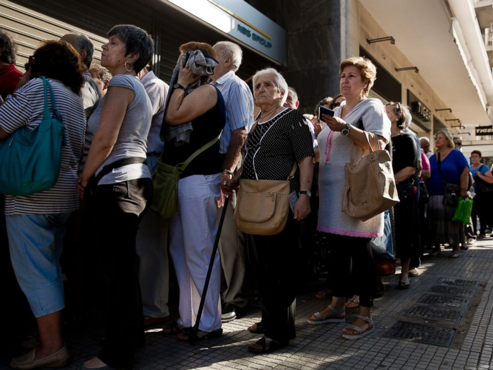 PHOTO: Pensioners line up as the wait to be allowed into a bank in Athens, July 1, 2015 , and withdraw a maximum 120 euros for the week, during capital controls in Greece.