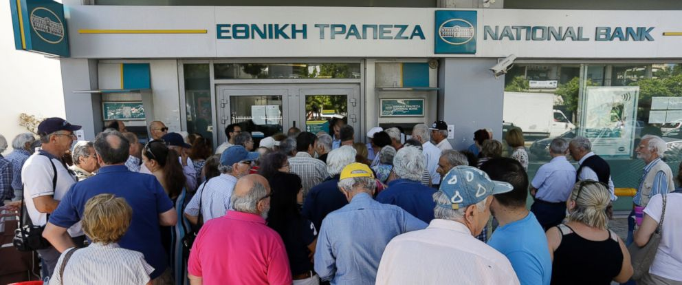 PHOTO: Pensioners wait to enter a bank as others queue to use the ATMs of the branch in Athens, Thursday, July 9, 2015.