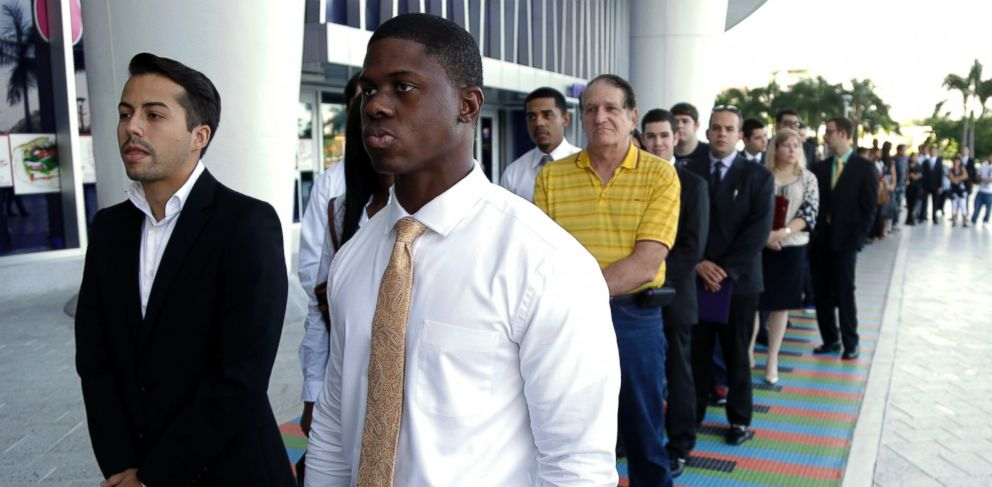 PHOTO: In this Oct. 23, 2013 file photo, Luis Mendez, left, and Maurice Mike,wait in line at a job fair held by the Miami Marlins, at Marlins Park in Miami.