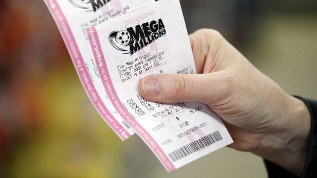 PHOTO: A customer at a convenience store holds her Mega Millions lottery tickets Friday, March 30, 2012, in Portland, Ore.