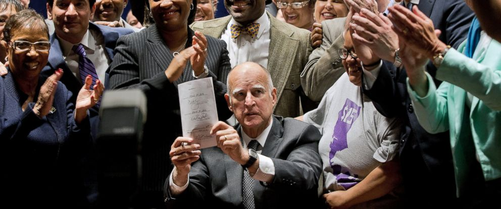 PHOTO: California Gov. Jerry Brown holds a signed bill creating the highest statewide minimum wage at $15 an hour by 2022 at the Ronald Reagan building in Los Angeles, April 4, 2016.