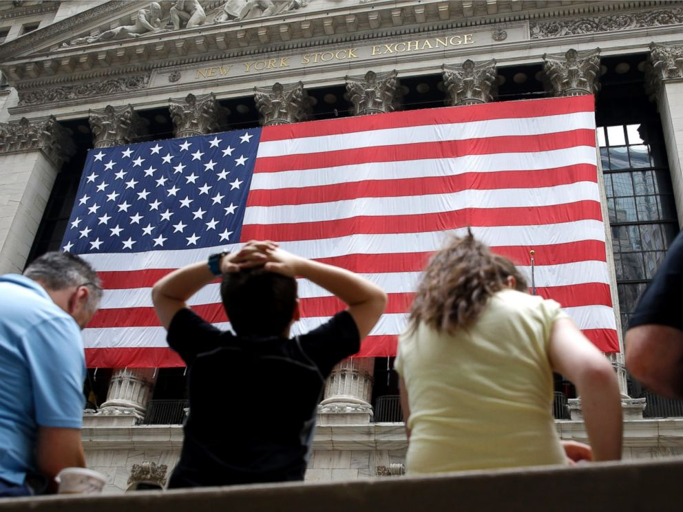 PHOTO: People sit on a bench near the New York Stock Exchange, July 8, 2015.