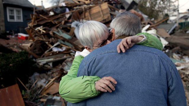 PHOTO: Sheila and Dominic Traina hug in front of their home which was demolished during Superstorm