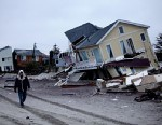 PHOTO: Man walks past damaged homes