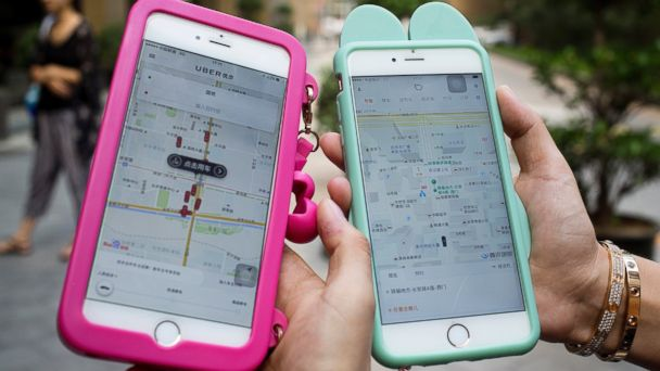 PHOTO: Women holding their smartphones show the ride-hailing apps Uber and Didi Chuxing at a residential compound in Beijing, China, Aug. 1, 2016.
