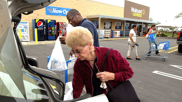 PHOTO: Michael Hall, Walmart Express customer service, helps Marian Faulkner with her bags at the new Walmart Express in Snow Hill, N.C.