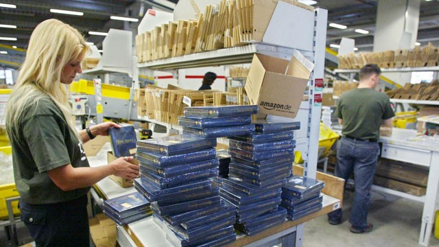 PHOTO: Employees of Amazon.de, the German branch of US online retailer Amazon.com, pack books into parcels ready to be sent to the clients, December 4, 2004 in Germany's Amazon distribution central in the western town of Bad Hersfeld.