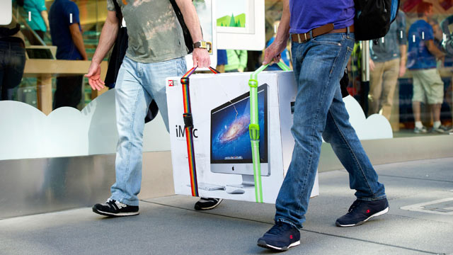 PHOTO: Customers carry an Apple Inc. iMac computer in front of an Apple Inc. store in San Francisco, Calif, April 19, 2013.