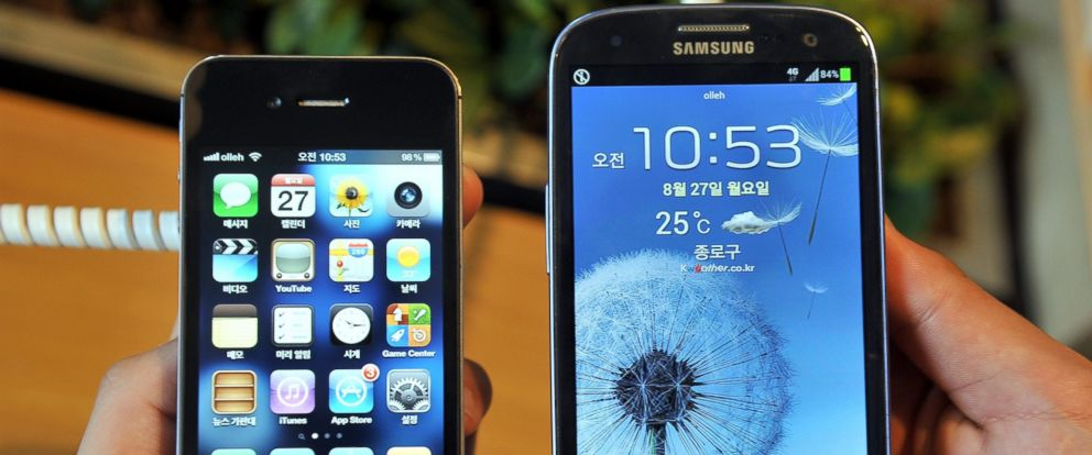 PHOTO: An employee shows an Apples iPhone 4s (L) and a Samsungs Galaxy S3 (R) at a mobile phone shop in Seoul on August 27, 2012.