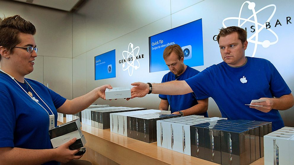 Employees hand off new iPhone 5 smartphones at an Apple Store in San