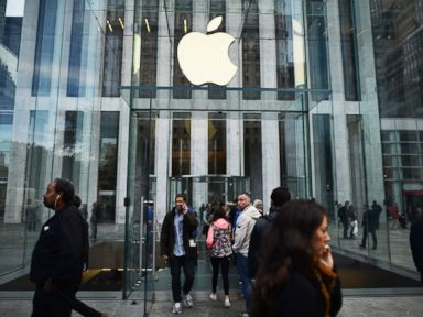 PHOTO: People walk past an Apple store in New York, Oct. 20, 2014.