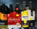 PHOTO: Six packs of Anheuser-Buschs Budweiser and Grupo Modelos Corona Extra beers sit on a shelf at the Chandi Wine and spirits store, Jan. 31, 2013 in Miami.
