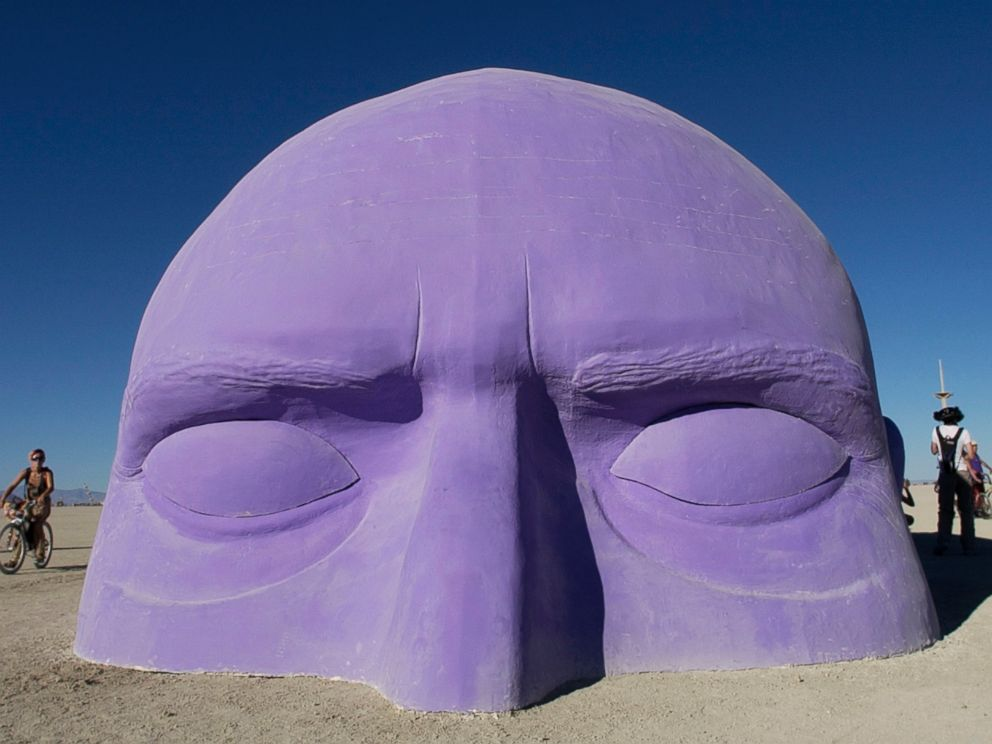 PHOTO:A giant head, one of many art installlations dotting the playa at Burning Man, appears to emerge from the sand, Aug. 30, 2005.