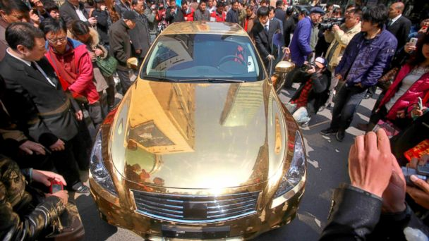 PHOTO: A crowd gather to admire a gold-plated Infiniti luxury sports car on display outside a jewellery store in Nanjing, east Chinas Jiangsu province on March 31, 2011.