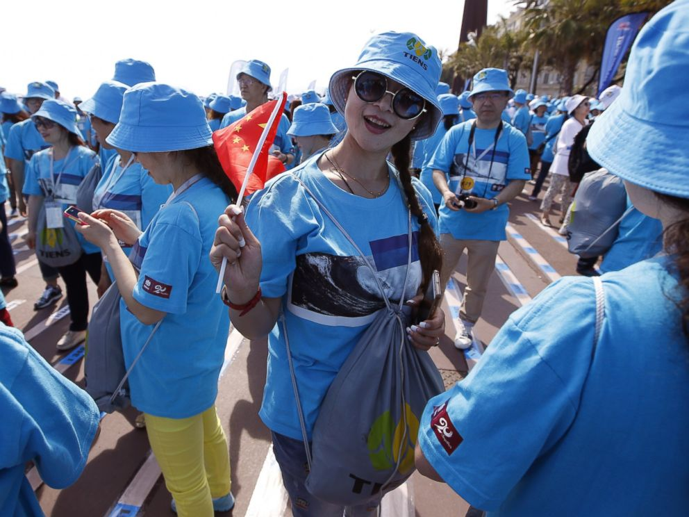PHOTO: Employees of the Chinese company Tiens attend a parade on May 8, 2015 in Nice, France.