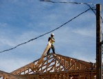 PHOTO: A worker installs roofing material while standing on the roof a house in Rancho Santa Fe, Calif., Dec. 21, 2012.