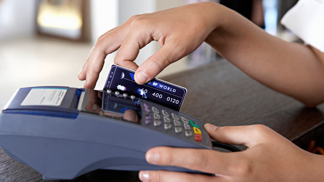 PHOTO: Young female shop assistant using credit card machine.