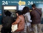 PHOTO: People withdraw money from a cash-point machine in the Cypriot capital Nicosia, March 17, 2013.