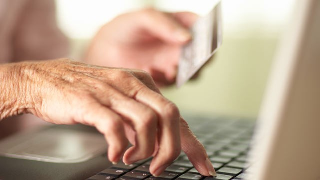 PHOTO: Close-up of Senior woman's hands using laptop and holding a credit card.