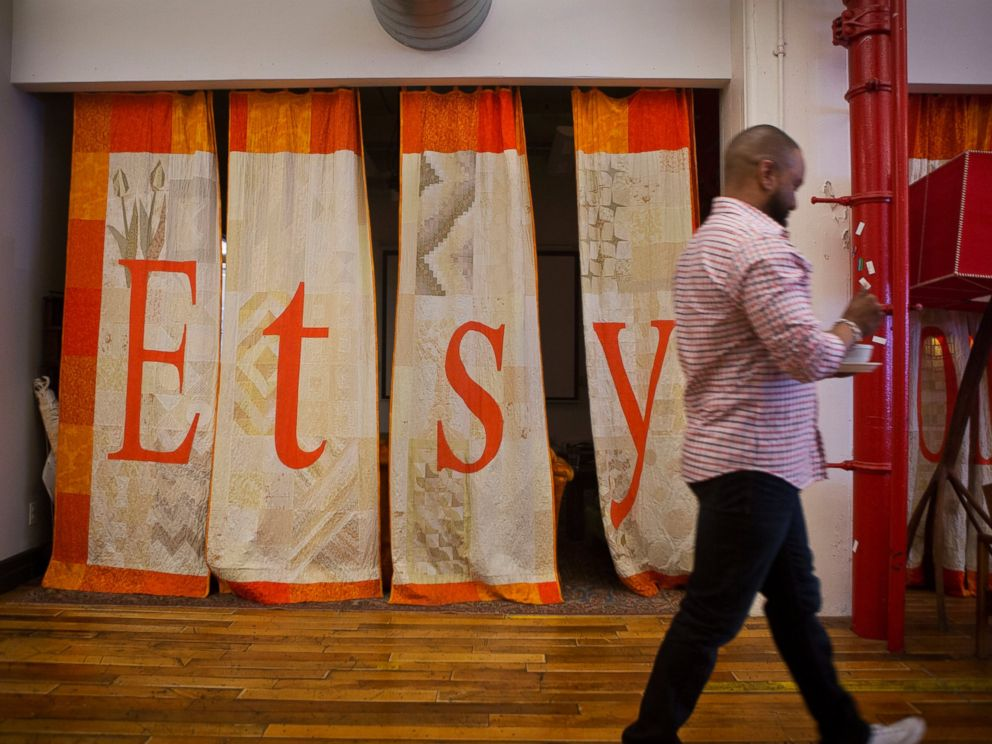 PHOTO: An employee walks past a quilt displaying Etsy Inc. signage at the companys headquarters in the Brooklyn borough of New York, May 4, 2015.