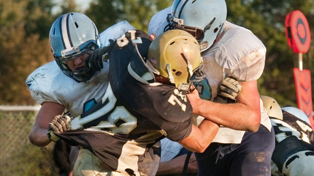 PHOTO: Football players block opponent
