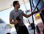 PHOTO: Jonathan Leon Rosen pumps gas into his vehicle at a Ugas station, April 24, 2012, in Miami.