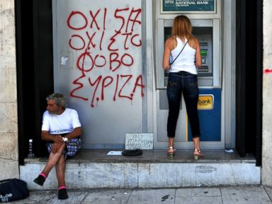 PHOTO: A woman withdraws money from an ATM machine next to a beggar and a graffiti reading No to fear in Thessaloniki, Greece, July 6, 2015.
