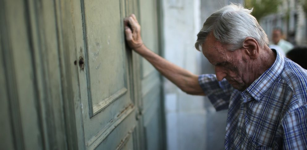 PHOTO: A senior citizen leans against the door of a closed bank as he queues up to collect his pension outside a National Bank of Greece branch in Kotzia Square, July 7, 2015 in Athens, Greece.