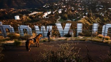 PHOTO: A woman stops with her horse to photograph the famous Hollywood Sign overlooking the Hollywood Hills on Jan. 31, 2012, in Los Angeles, Calif.