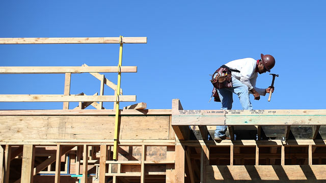PHOTO: A construction worker uses a hammer at a new housing deve