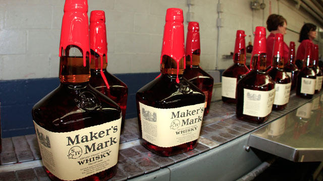 PHOTO: Bottles of Makers Mark Distillery Inc. bourbon whisky sit on a conveyor belt after being hand dipped with their signature red wax at their distillery in Loretto, Kentucky, U.S., Jan. 4, 2011.