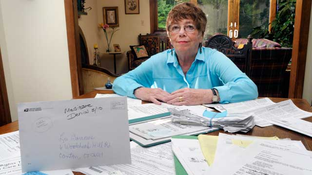 PHOTO: Lee Barrows poses for a portrait with medical bills at her home in Canton, Connecticut, U.S., on July 2, 2010.