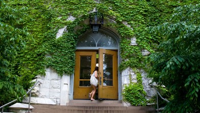 PHOTO: College student walking through door of Northwestern University building.
