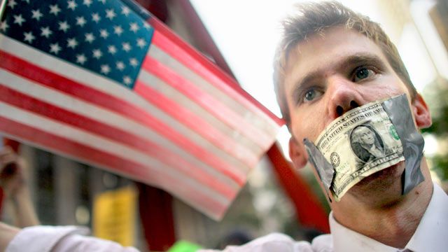 PHOTO: A protester wears a dollar bill over his mouth at the start of a march by demonstrators opposed to corporate profits on Wall Street on Sept. 30, 2011 New York City.