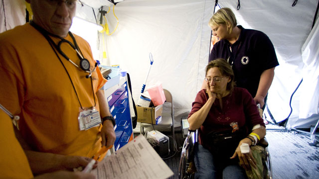 PHOTO: An unidentified woman is wheeled out of the emergency tent to be taken to hospital, at the Remote Area Medical (RAM) clinic in Wise, Virginia. Rural families, most with little or no insurance, lined up for hours to receive free health care from hu