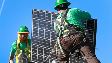 PHOTO: Lead installers for SolarCity Charles Groves (R) and Matt Parra (L) install solar electrical panels on the roof of a home, March, 31, 2011 in Palo Alto, California,