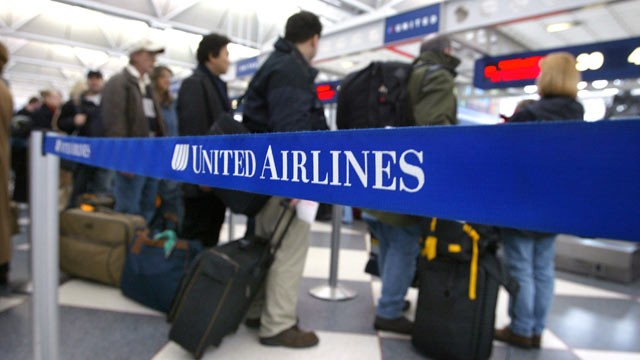 PHOTO: Air travelers stand in line at the United Airlines terminal at O'Hare International Airport in Chicago, Illinois.