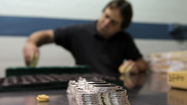 PHOTO: A worker sorts trays of silver blanks th
